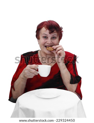 Senior woman in red dress sits behind table with coffee cup in hand and eats cookie. Portrait isolated on white background