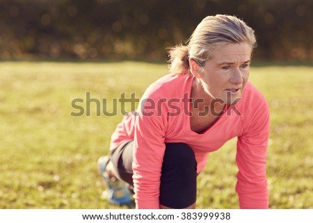 Senior woman in sportswear, doing a warm-up stretching exercise on a sunlit morning, looking ahead of her with an expression of focus and determination - stock photo