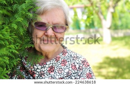 Senior woman in sunglasses smiling in garden. - stock photo