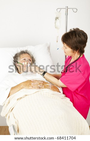 Senior woman in the hospital with lung disease, getting oxygen from a nurse. - stock photo