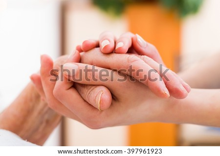 Senior woman in the nursing home getting support from a younger person.