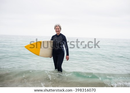 Senior woman in wetsuit standing in water with surfboard on the beach on a sunny day - stock photo