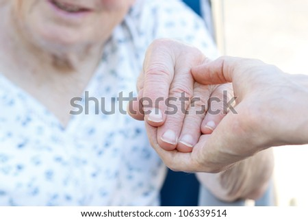 Senior woman in wheelchair holding hands with caretaker - stock photo