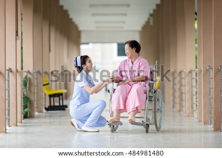 Senior woman in wheelchair talking to a nurse in a hospital