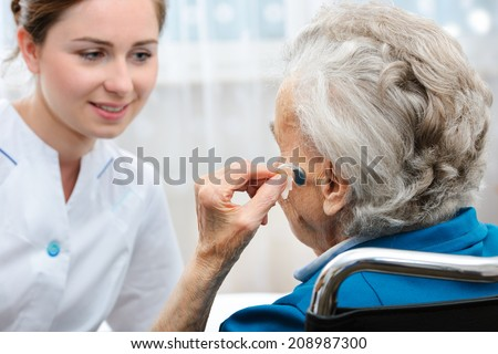 Senior woman inserts hearing aid in her ear - stock photo