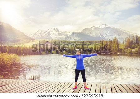 Senior woman is exercising on the pier by the tarn in beautiful mountains, hills and hotel in background - stock photo