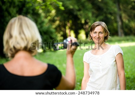 Senior woman is taking video of her adult daughter in nature - stock photo