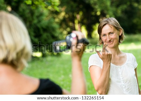 Senior woman is taking video of her adult daughter in nature with camcorder - stock photo