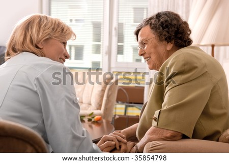 Senior woman is visited home by her doctor or caregiver at home - stock photo