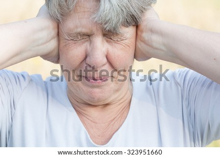 Senior woman keeps her ears shut - stock photo
