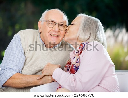 Senior woman kissing on man's cheek while sitting at nursing home porch - stock photo