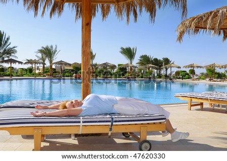 Senior woman lie on chaise longue , near water pool. - stock photo