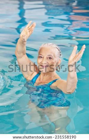 Senior woman lifting her arms in aqua fitness class in a swimming pool - stock photo