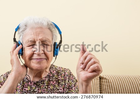 senior woman listening music with headphones - stock photo