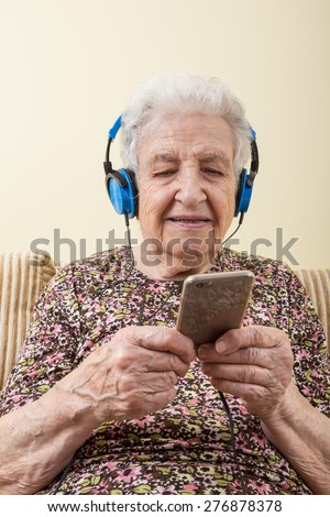 senior woman listening music (with smartphone / ipod)