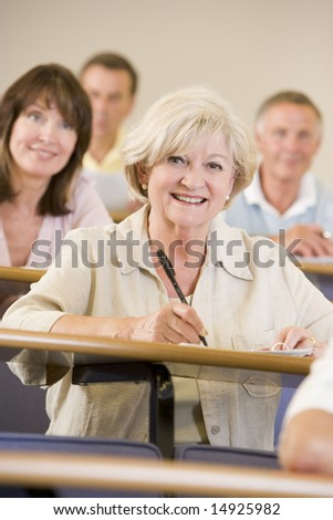 Senior woman listening to a university lecture - stock photo