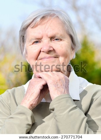 Senior woman looking and smiling in garden on blue sky. MANY OTHER PHOTOS FROM THIS SERIES IN MY PORTFOLIO.
