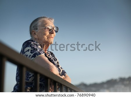 Senior woman looking forward over blue sky. - stock photo