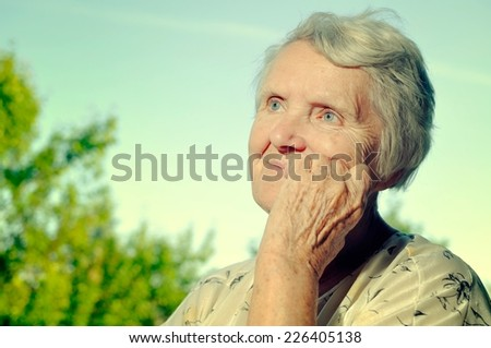 Senior woman looking on sky and smiling. Vintage style. - stock photo