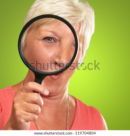 Senior Woman Looking Through A Magnifying Glass On Green Background - stock photo