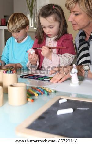 Senior woman making watercolors with children - stock photo