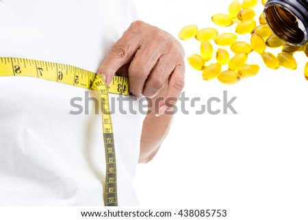 Senior woman measuring her waist with fish oil capsules on white.