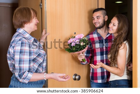 Senior woman meeting  young couple with flowers at the door - stock photo