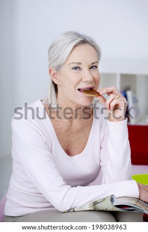 Senior woman nibbling while reading a magazine.