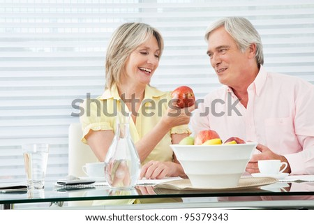 Senior woman offering her husband a red apple