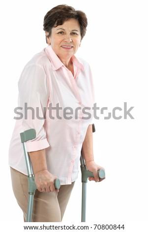 senior woman on crutches smiling - stock photo