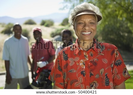 Senior woman on golf course, (portrait), family in background - stock photo