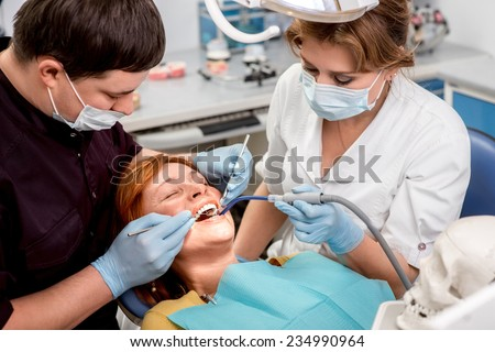 Senior woman on the operation in the dental office. Dentist with assistant examining implants teeth - stock photo