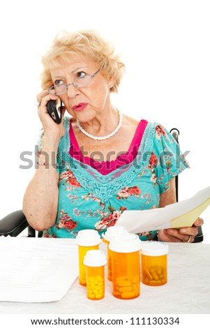 Senior woman on the phone discussing her medical bills with the health insurance company.  White background. - stock photo