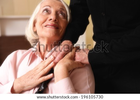 Senior woman on wheelchair taking her husband's hand. - stock photo