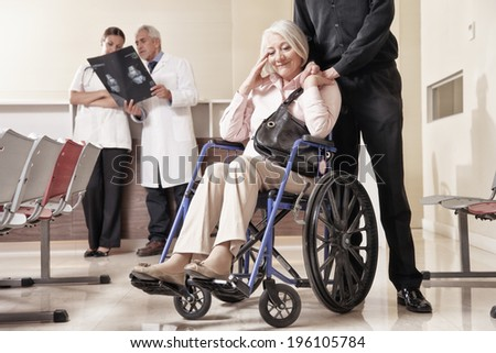 Senior woman on wheelchair with her husband and doctors analyzing x-ray in background. - stock photo