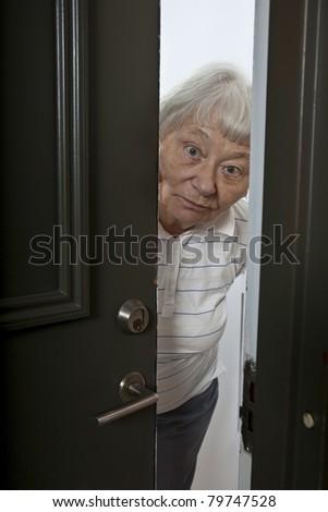 Senior woman opening front door - stock photo
