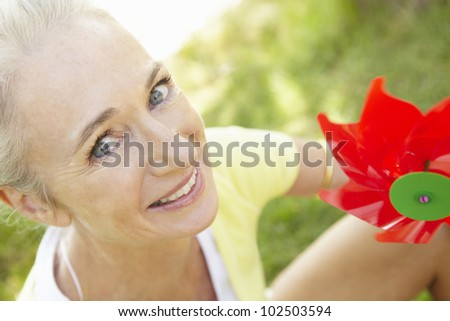 Senior woman outdoors with toy windmill - stock photo