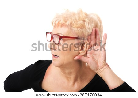 Senior woman overhears a conversation - stock photo