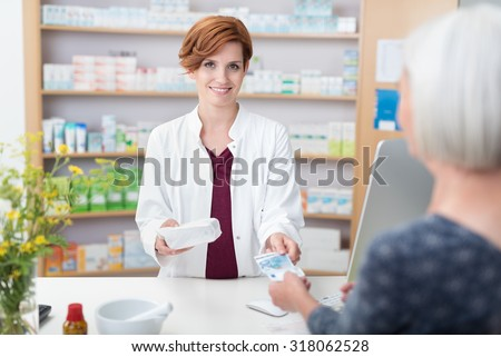 Senior woman patient paying for her medication in a pharmacy handing the pretty smiling female pharmacist a banknote - stock photo