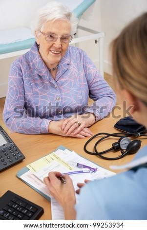Senior woman patient with UK nurse - stock photo