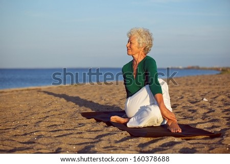 Senior woman performing a yoga routine on the beach. Elder woman doing stretching exercise on sandy beach with lots of copyspace - stock photo