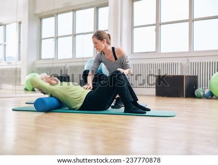Senior woman performing back exercise on a foam roller being assisted by her personal trainer at gym. Physical therapist helping elder woman at rehab. - stock photo