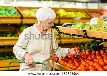 Senior woman picking out some vegetables in supermarket
