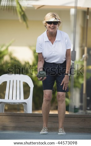 Senior woman playing bocce ball and smiling - stock photo