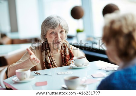 Senior woman playing cards with her friend