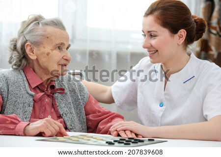 Senior woman playing checkers with a nurse in a retirement home - stock photo