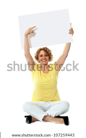 Senior woman pointing at blank ad board over her head