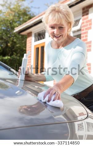 Senior Woman Polishing Car With Cloth - stock photo