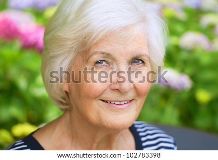 Senior woman portrait, outdoors, in front of the garden, smiling to camera - stock photo