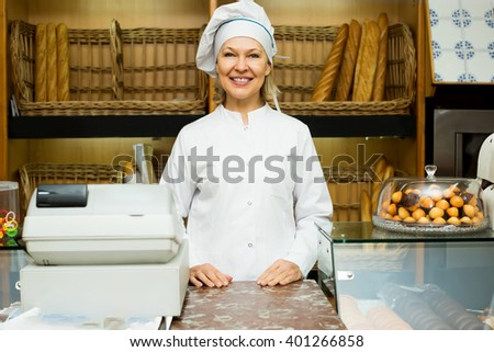 Senior woman posing in bakery with baguettes and buns - stock photo